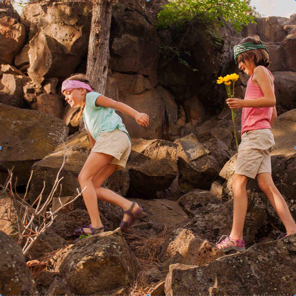 Two young girls walking among the Juniper Trees